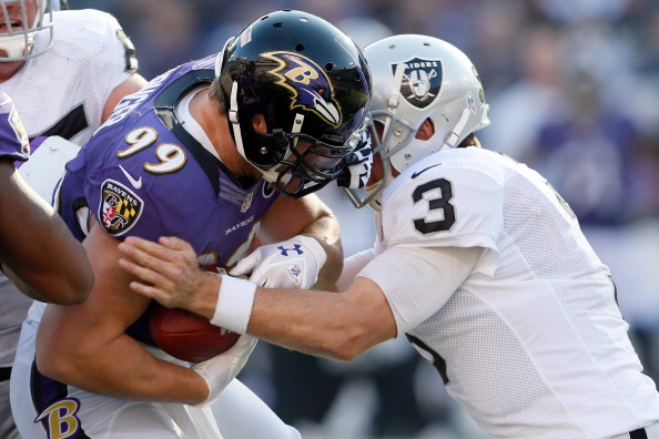 BALTIMORE, MD - NOVEMBER 11:  Quarterback Carson Palmer #3 of the Oakland Raiders tackles linebacker Paul Kruger #99 of the Baltimore Ravens after Kruger intercepted Palmer's pass during the first half of their gameat M&T Bank Stadium on November 11, 2012 in Baltimore, Maryland.  (Photo by Rob Carr/Getty Images)