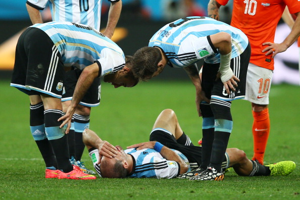 Pablo Zabaleta of Argentina lies on the pitch after a collision as teammates Rodrigo Palacio (L) and Lucas Biglia of Argentina look on during the 2014 FIFA World Cup Brazil Semi Final match between the Netherlands and Argentina (credit: Clive Rose/Getty Images)