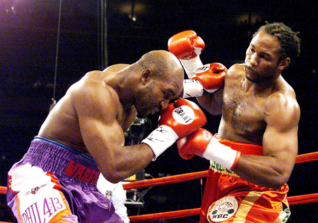 IBF and WBA Heavyweight Champion Evander Holyfield (L) ducks out of the way of a punch by WBC heavyweight Champion Lennox Lewis.