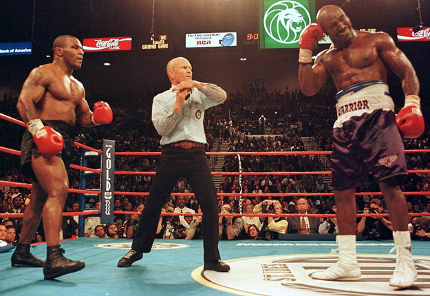 Referee Lane Mills (C) stops the fight in the third round as Evander Holyfield (R) holds his ear as Mike Tyson (L) watches.