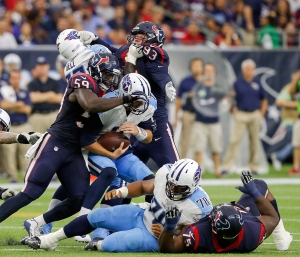 HOUSTON, TX - NOVEMBER 01: Zach Mettenberger #7 of the Tennessee Titans is sacked by Whitney Mercilus #59 of the Houston Texans at NRG Stadium on November 1, 2015 in Houston, Texas. (Photo by Bob Levey/Getty Images)