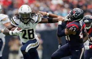 HOUSTON, TX - NOVEMBER 27: Melvin Gordon #28 of the San Diego Chargers gives a stiff arm to Quintin Demps #27 of the Houston Texans in the second quarter at NRG Stadium on November 27, 2016 in Houston, Texas. (Photo by Tim Warner/Getty Images)